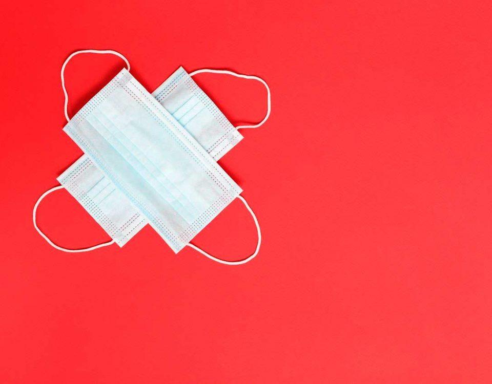 mascarillas cruzadas formando una cruz sobre un fondo rojo